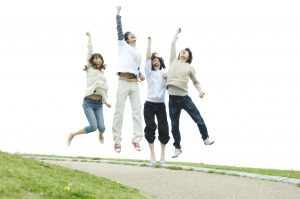 Young people jumping to joy with their hands raised
